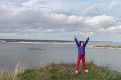 Meisje op de rand van de heuvel Een meisje op de rand van een klip boven de rivier overwinning kracht slag strijd Stock Foto