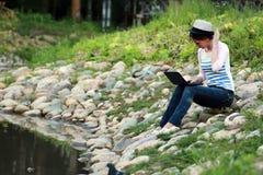 Meisje op de rotsrivier Stock Afbeelding