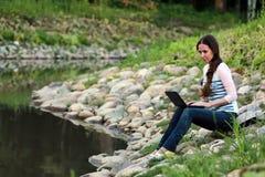 Meisje op de rotsrivier Stock Fotografie