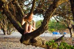 Meisje op de strandboom Stock Afbeeldingen