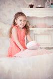 Meisje op een bed met roze doos Stock Foto's