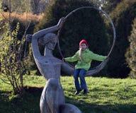 Meisje op een beeldhouwwerk Stock Fotografie