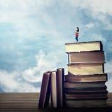 Meisje op een boekenstapel stock foto