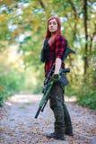 Meisje op een bosweg met een geweer stock foto's