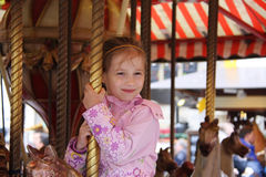 Meisje op een carrousel Stock Afbeeldingen