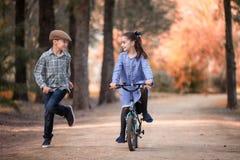 Meisje op een fiets en jongen die naast op de weg van een park lopen royalty-vrije stock fotografie