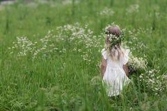 Meisje op een gang op een heldere de zomerdag Portret van een klein meisje met een kroon van kamilles op haar hoofd stock afbeeldingen