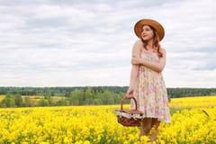 Meisje op een gebied van bloemen met mand en een hoed Royalty-vrije Stock Afbeeldingen