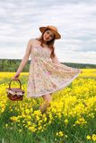 Meisje op een gebied van bloemen met mand en een hoed Stock Fotografie