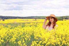 Meisje op een gebied van bloemen met mand en een hoed Stock Foto's