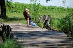 Meisje op een houten bridg stock afbeelding