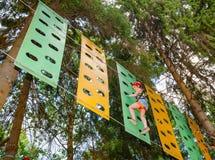Meisje op een kabelscursus in een treetop avonturenpark die hangende kabelhindernis overgaan royalty-vrije stock afbeeldingen