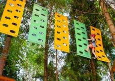 Meisje op een kabelscursus in een treetop avonturenpark die hangende kabelhindernis overgaan stock foto's