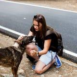 Meisje op een kant van de weg met een dakloze hond, die samen reizen royalty-vrije stock fotografie