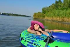 Meisje op een opblaasbare boot in een hoed Stock Foto