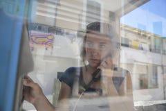 Meisje op een openbare payphone cabine van buiten Stock Fotografie