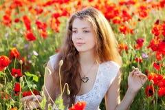 Meisje op een papavergebied Stock Afbeelding