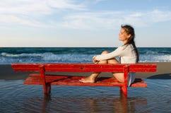Meisje op een rode bank Stock Foto