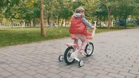 Meisje op een roze fiets stock video