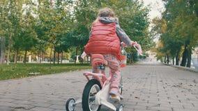Meisje op een roze fiets stock footage