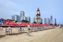 Meisje op een strand met Coca-Cola parasols, Yantai, China Stock Fotografie