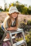 Meisje op een trapladder op feegebied van lavendel Royalty-vrije Stock Afbeeldingen
