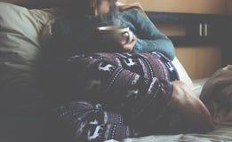 Meisje op een wit bed met een Kop van koffie stock afbeeldingen