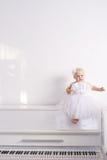Meisje op een witte piano Stock Foto's