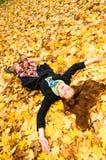 Meisje op esdoornbladeren Stock Foto