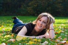 Meisje op gras en esdoornbladeren Stock Afbeeldingen