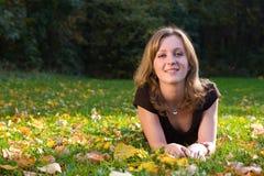 Meisje op gras en esdoornbladeren Royalty-vrije Stock Foto's