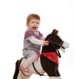 Meisje op haar eerste stuk speelgoed paard dat op een wit wordt geïsoleerd Stock Afbeelding
