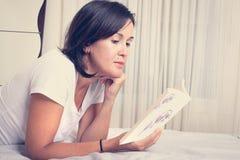 Meisje op het bed die een boek lezen royalty-vrije stock foto's
