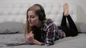 Meisje op het bed met hoofdtelefoons stock footage