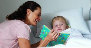 Meisje op het boek van de bedlezing met haar moeder stock video