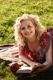 Meisje op het gras met een boek Stock Foto's