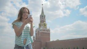 Meisje op het rode vierkant met uw telefoon stock video