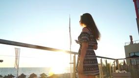 Meisje op het strand bij zonsondergang met haar haar in de wind stock footage