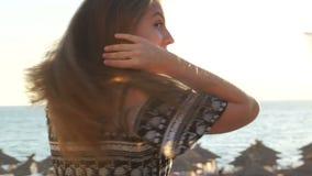 Meisje op het strand bij zonsondergang met haar haar in de wind stock videobeelden