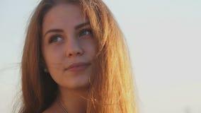 Meisje op het strand bij zonsondergang met haar haar in de wind stock video