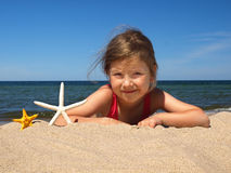 Meisje op het strand met zeesterren Stock Afbeelding