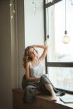 Meisje op het venster met een kop van koffie en tijdschrift Royalty-vrije Stock Foto's
