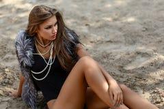 Meisje op het zand in een bontvest Stock Afbeelding