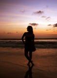 Meisje op het zonsondergangstrand Stock Foto's
