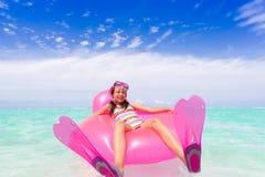 Meisje op luchtmatras in overzees royalty-vrije stock afbeeldingen
