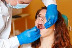 Meisje op onderzoek bij de tandarts stock foto's