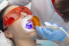 Meisje op onderzoek bij tandartsbehandeling van carieuze tand de arts gebruikt een spiegel op het handvat en een boriummachine; m stock afbeelding