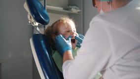 Meisje op ontvangst bij de tandarts, stomatologist die en de en kind` s tanden, meisje schoonmaken water geven die glimlachen spr stock footage
