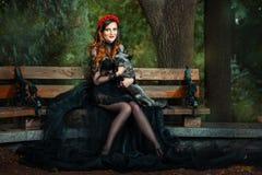 Meisje op parkbank met een vos stock fotografie