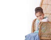 Meisje op rieten stoel wordt gesteld die Royalty-vrije Stock Foto